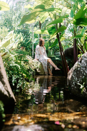Water One Person Plant Women Nature Real People Lake Day Tree Adult Leisure Activity Rear View Lifestyles Waterfront Full Length Reflection Growth Leaf Outdoors Hairstyle