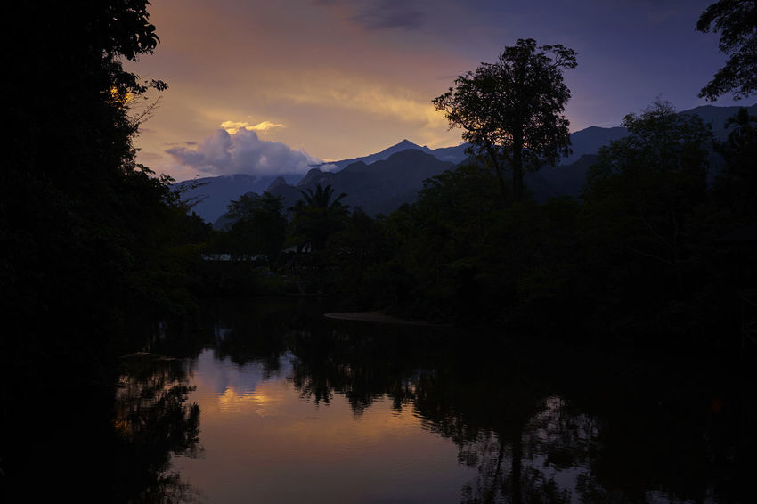 Dramatic sunset over a river in the Gunung Mulu Nationa Park in Borneo Beauty In Nature Calm Cloud - Sky Dark Growth Majestic Malaysia Moon Mountain Mountain Range Nature No People Non-urban Scene Outdoors Rainforrest Reflection Reflection Remote Standing Water Sunset Tranquil Scene Tranquility Tree Tropical Climate Water