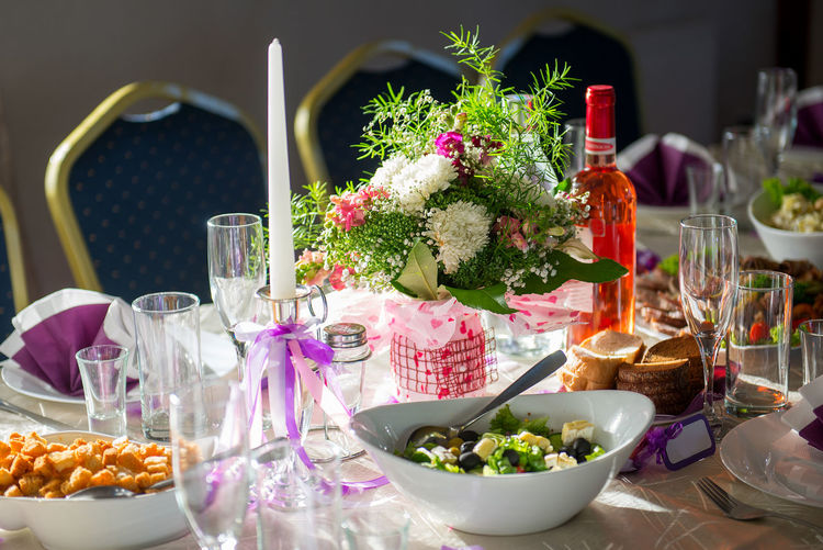 Close-up of bouquet with food and place setting on table