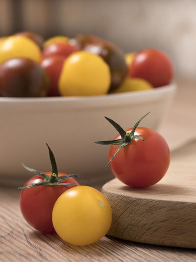 Cherry tomatoes, red,yellow and kamato on a wooden table. Fresh; Food; Healthy; Ripe; Red; Vegetable; Cherry; Tomato; Vegetarian; Yellow; Diet; Orange; Variety; Colorful; Different; Health; Green; Organic; Ingredient; Many; Summer; Small; Juicy; Raw; Nature; Tomatoes; Color; Natural; Closeup; Background; Agricul Fruit Food Food And Drink Healthy Eating Wellbeing Tomato Freshness Table Vegetable Still Life Cherry Tomato Red Yellow Close-up Indoors  No People Wood - Material Focus On Foreground Apple - Fruit Orange Color Orange Ripe