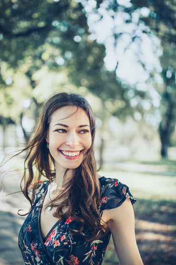 Portrait of cheerful optimistic brunette in a flower dress in the park, smiling. close up.