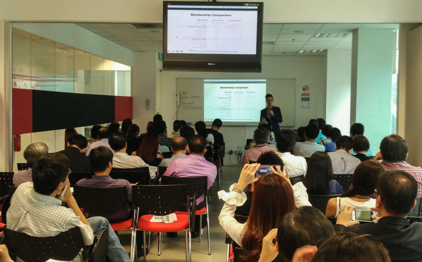 People attend a talk at a seminar room. Learning Networking event speaker Crowd Student Chairs And Tables Audio And Visual Television