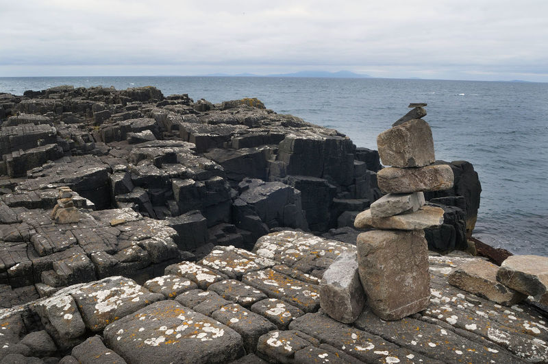Cairn on the rocky shoreline at Neist Point, Isle of Skye. On the horizon is the Outer Hebrides. Cairn Calm Cliff Coast Highlands Horizon Over Water Neist Point No People Non-urban Scene Remote Rock Rock - Object Rock Formation Scotland Sea Sky Skye Stone Water