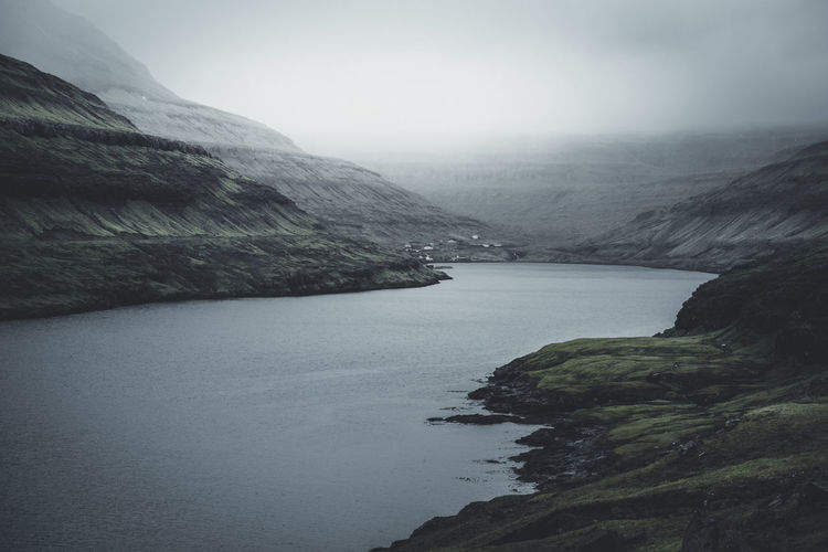 """Funningsfjørður. """"Fjørður"""" is the Faroese word for """"fjord"""". Only 52 people live here at the end of this fjord who is created by glacial erosion in the last glacial period. Location: Funningsfjørður, Faroe Islands Equipment: Fujifilm X-T2 + XF14 F2.8 R Funningsfjørður Wanderlust Beauty In Nature Day Faroe Islands Fjord Fjørd Fog Färöer Globetrotter Landscape Mood Moody Mountain Nature No People Outdoors River Scenery Scenics Sky Tranquil Scene Tranquility Water Waterfront"""