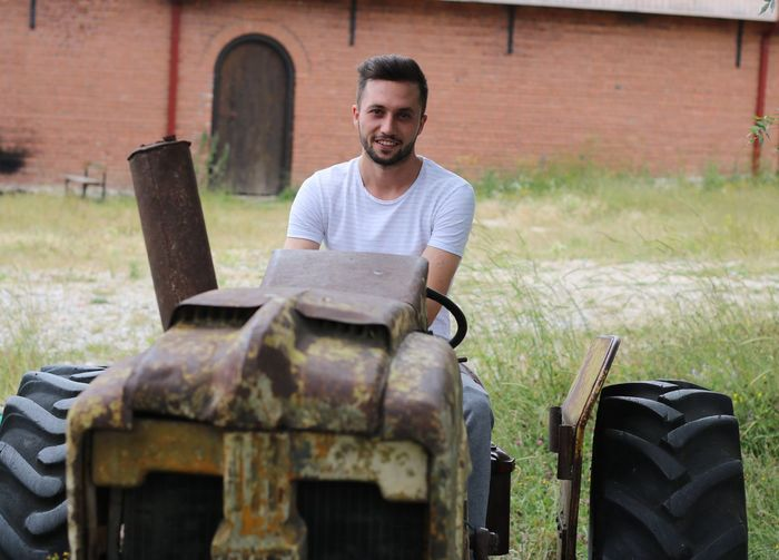 Portrait of young man driving tractor in farm