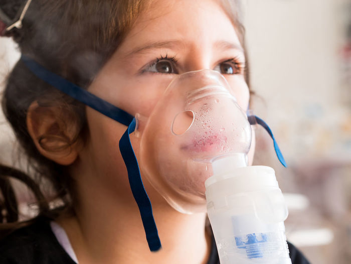 Cute small girl inhaling with oxygen mask close up Girl Kid Child Childhood Ill Small Little Cute Caucasian Inhaler Inhaling Inhalation Oxygen Mask Health Medicine Bronchitis Flu Home Close Up Indoors  Asthma Asthmatic Medical Treatment Allergy Patient Care Breath Headshot Close-up