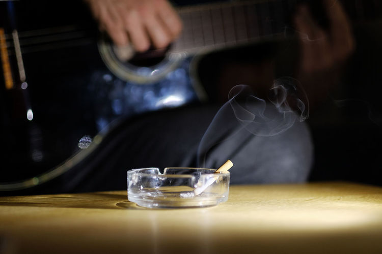 Close-Up Of Cigarette In Ashtray With Man In Background
