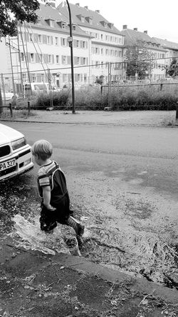 The Street Photographer - 2016 EyeEm Awards Boy Rainy Days Puddle Springtime Fun Children Children Playing Rubber Boots After The Rain Streetphotography Street Photography Street Life Blackandwhite Black And White Blackandwhite Photography Black & White