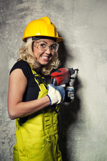 Portrait Of Smiling Female Worker Drilling In Concrete Wall