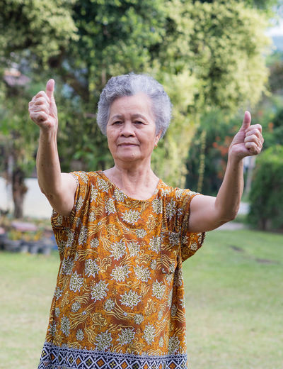 Elderly woman with arms raised standing outdoors
