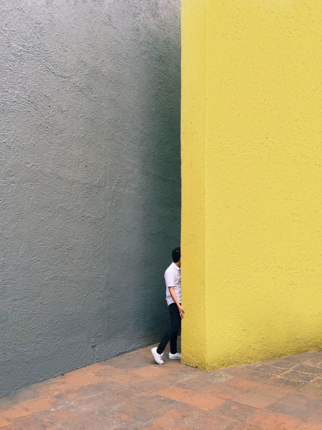 Man standing by yellow wall