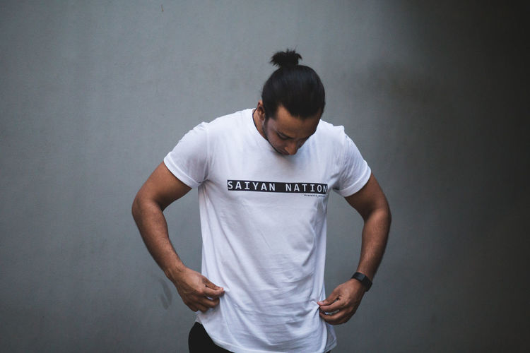 Saiyan Nation (V) One Person Standing Text Casual Clothing Western Script Front View Real People Three Quarter Length Young Adult Studio Shot Waist Up T-shirt Young Men Lifestyles Looking Down Looking White Color Communication Fashion Urban athleisure Portrait