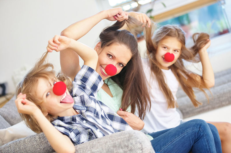 Portrait of family wearing clown nose at home