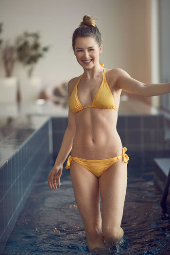 Young blond woman in bikini smiling at the camera SlenderMan Slim Bathcloth Beautiful Woman Bikini Blond Hair Cheerful Fit Focus On Foreground Lifestyles Looking At Camera One Person Portrait Relaxation Shapely Smiling Smiling Face Swimmingpool Water Young Adult Young Women