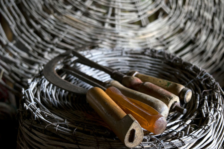 old agrarian instruments on a wicker basket Agrarian Agriculture Ancient Antique Objects Wicker Background Basket Instruments Old Screwdriver Scythe Sickle Tools