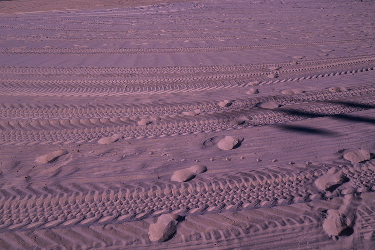 High angle view of tire tracks and footprints at beach