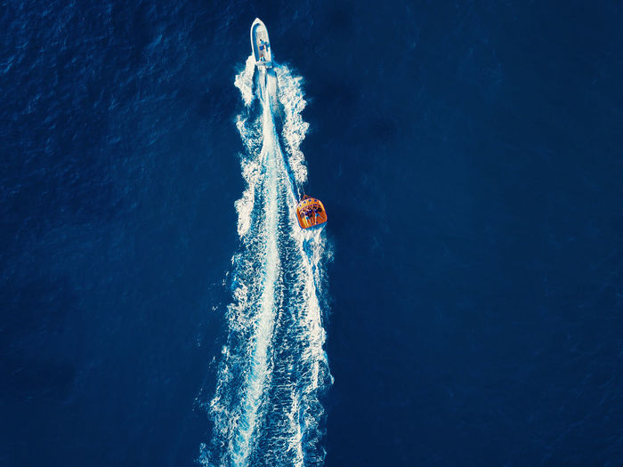 Aerial view of a watersports speedboat and people having fun while riding on a floating sofa.