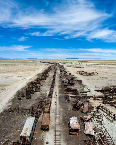 Abandoned trains on land against sky
