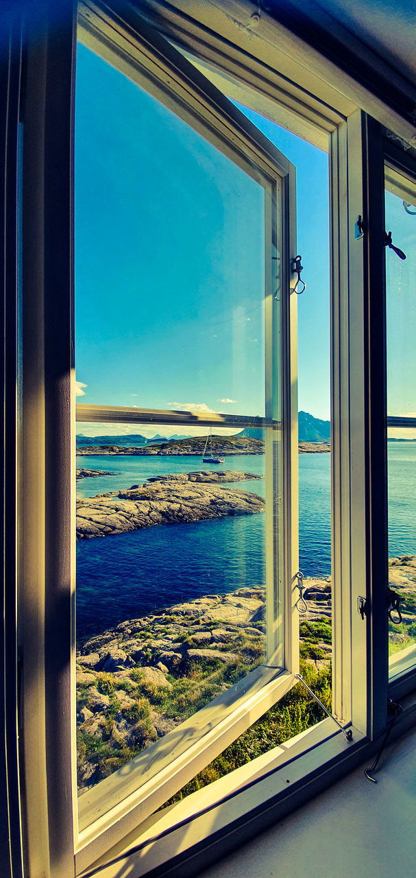 SCENIC VIEW OF SEA AGAINST SKY SEEN THROUGH WINDOW