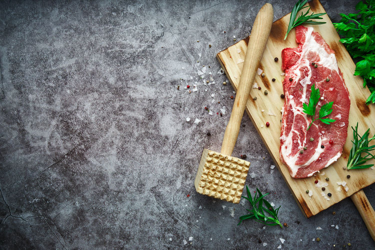 Raw beef steak with tomato, garlic, pepper, salt and rosemary on frying pan on a dark background.