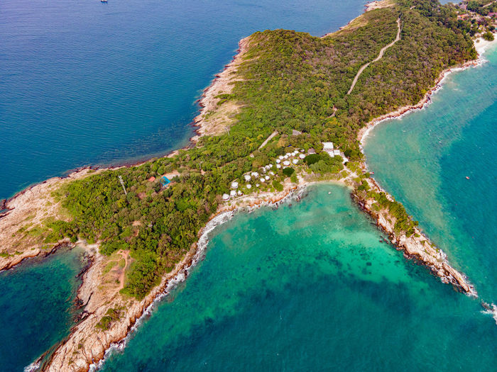 Top view of island and beautiful blue seashore and rocky on coast and white bungalow on the beach