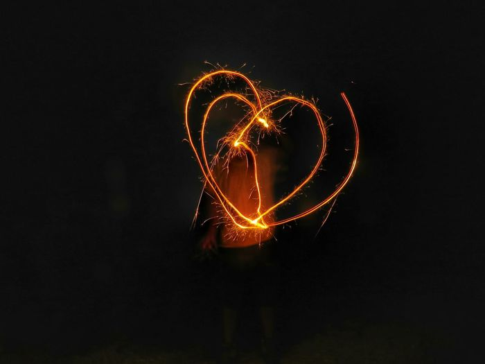 Man Making Heart Shape Light Painting From Sparklers At Night