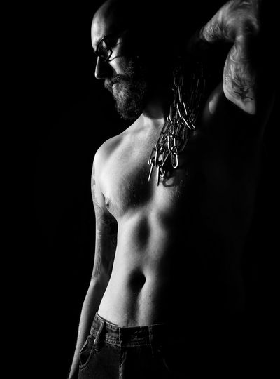 Full length of shirtless man against black background