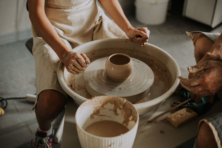 Close-up shot of ceramic cup spinning on potters's wheel and hands molding clay