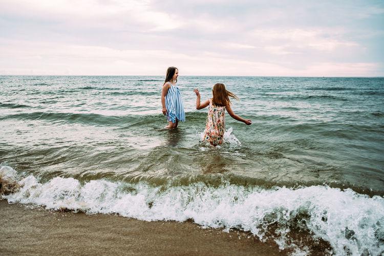 Women on beach against sky