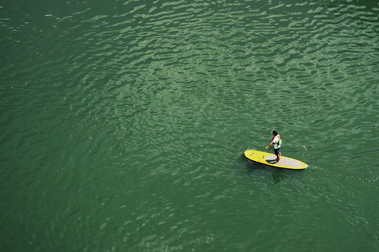 High angle view of man standing on surfboard in sea