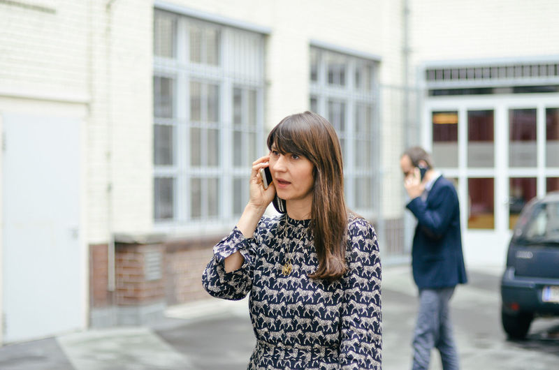 Professional woman using mobile phone in city