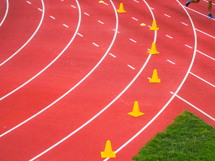 High angle view of yellow traffic cones on sports track