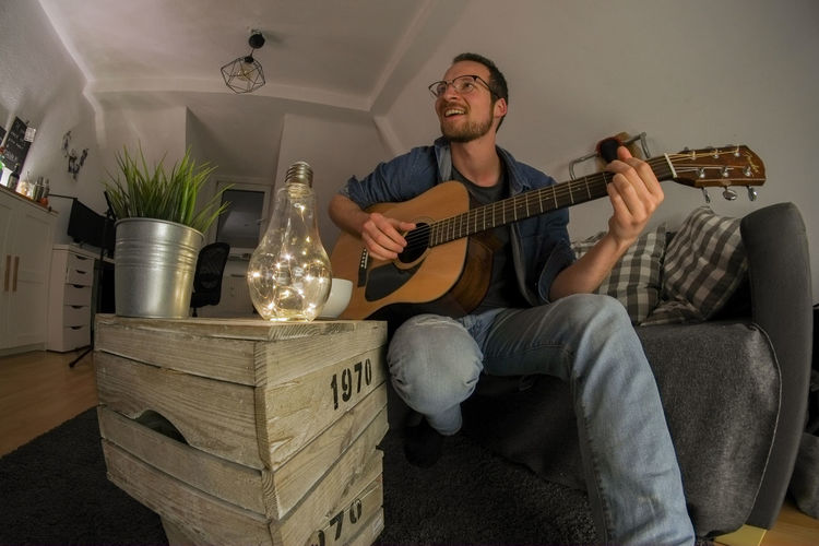 Young male playing acoustic guitar in cosy living room Cosy Light Cosy Living Room Acoustic Guitar Guitar Player Guitar Playing Guitarist Chord Sofa Couch Evening Dark Analogue Sound