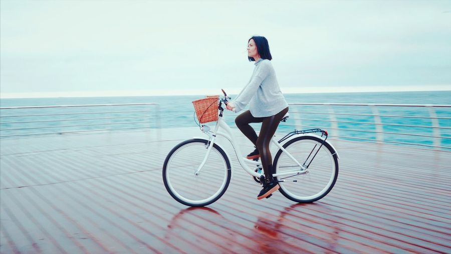 Woman riding bicycle on boat deck in sea against sky