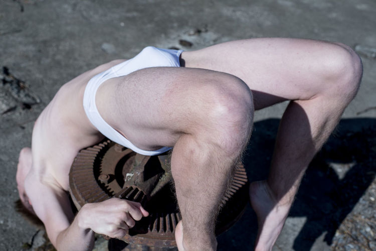 High angle view of shirtless man lying over metallic equipment