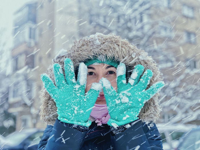 Portrait of woman with ice cream cone in snow