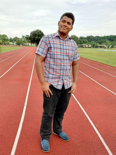 Smiling young man standing on sports track