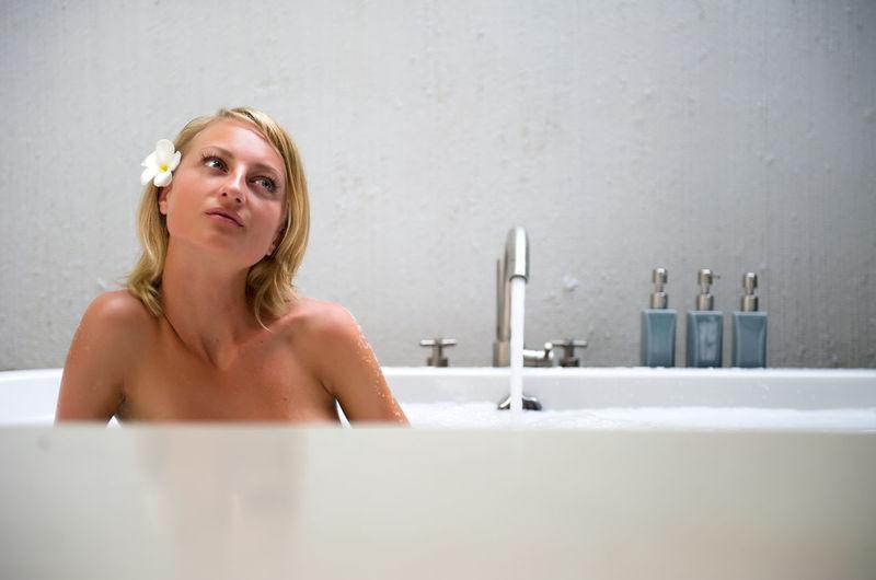 Shirtless Woman Sitting In Bathtub