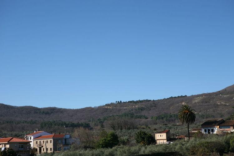 Houses on mountain against clear blue sky