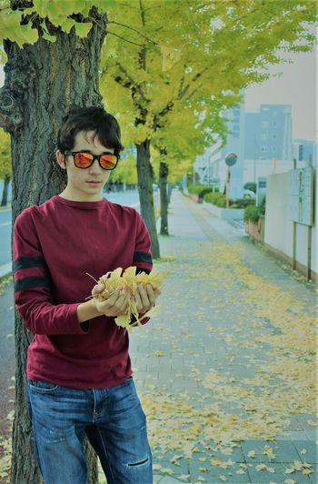 Portrait Of Teenage Boy Wearing Sunglasses While Holding Autumn Leaves On Sidewalk