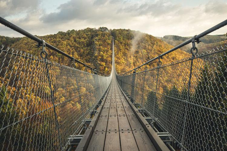Footbridge in forest against sky