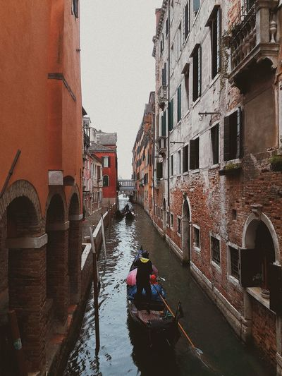 People on boat in canal amidst buildings in city