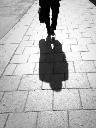 Shadow of a person walking on sidewalk