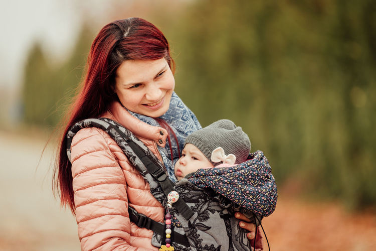 Smiling mother with daughter outdoors during winter