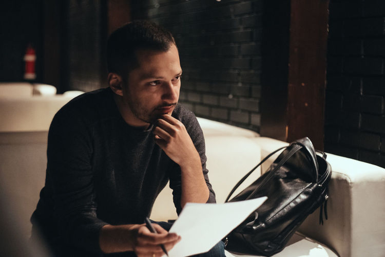 On an interview Adult Casual Clothing Contemplation Focus On Foreground Front View Indoors  Leisure Activity Lifestyles Looking Looking Away Males  Men One Person Portrait Real People Sitting Waist Up Young Adult Young Men