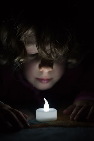 little girl fascinated by an artifical light Black Background Candle Childhood Close-up Concentration Flame Front View Headshot Illuminated Indoors  One Person People Real People