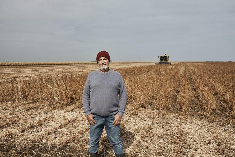 Portrait of man standing on field against sky
