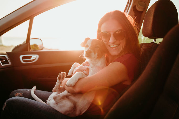 Woman sitting with dog in car