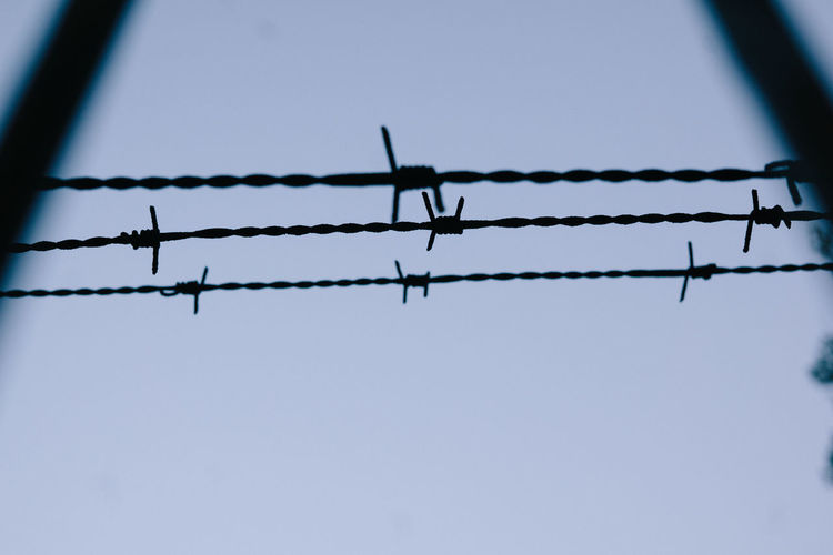 Low angle view of silhouette barbed wire against clear sky