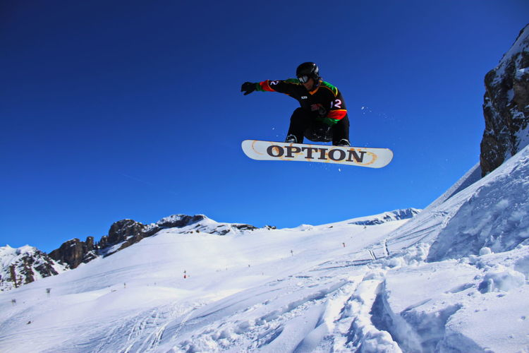 Man jumping on snowcapped mountain against sky